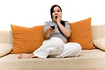 Girl sitting on sofa watching TV, shocked